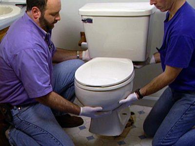 Men installing toilet