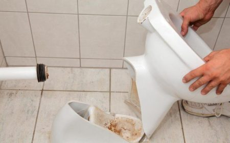 Man's hand while holding broken toilet