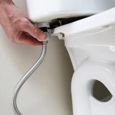 Man's hand holding toilet water pipe